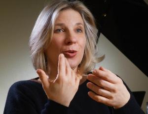 Stimmtrainerin Monika Drux macht mit Händen und Mund eine Stimmübung vor