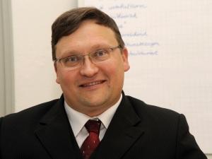 Akademie-Leiter Andreas Franken sitzt an Dozenten-Tisch