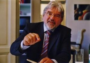 Akademie-Gründer Friedhelm Franken sitzt am Besprechungstisch und gestikuliert mit der rechten Hand