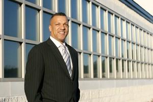 selbstbewusster Geschäftsmann vor Firmengebäude