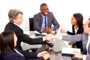 5 Geschäftsleute am Besprechungstisch, die einander anlächeln und teilweise die Hände reichen