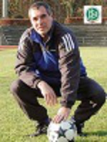 Motivationstrainer Jorge Martins hockt mit Ball auf dem Fußballplatz