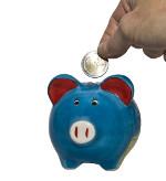 Hand wirft Münze in Sparschwein