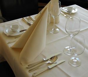 eingedeckter Tisch mit aufrecht stehenden Servietten