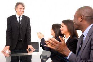 Präsentator am Besprechungstisch erhält Applaus von Kollegen