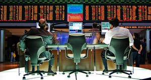zwei Börsenmakler beobachten konzentriert die Entwicklung von Aktienkursen auf einer großen Anzeige
