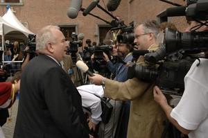 von Journalisten mit Mikros und Kameras umringter Politiker gibt ein Interview