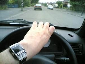 Hand mit Uhr an Lenkrad eines Autos und Blick durch die Windschutzscheibe