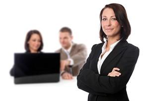 selbstbewusste Geschäftsfrau mit verschränkten Armen im Vordergund,  am Laptop arbeitende Mitarbeiter im Hintergrund