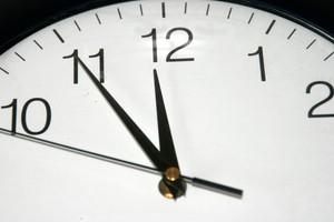 analoge Uhr zeigt 5 vor 12