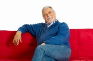 älterer Herr auf rotem Sofa